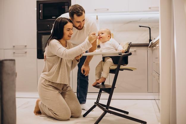 Mama mit papa füttert ihr baby in einem fütterungsstuhl