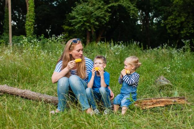 Mama mit zwei kindern sitzt im wald auf einem umgestürzten baumstamm und isst mais