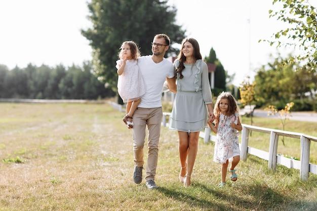 Mama, papa, die töchter umarmen, gehen gerne im freien spazieren und schauen sich die natur an. junge familie, die zeit zusammen im urlaub, im freien verbringt. muttertag, vatertag, babytag.