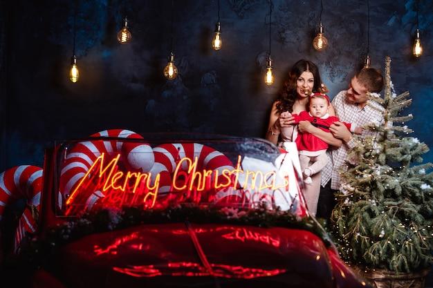 Mama, papa und baby haben spaß in der nähe von weihnachtsbaum und retro rotes auto. eltern mit einer kleinen tochter in einer weihnachtsfotosession.