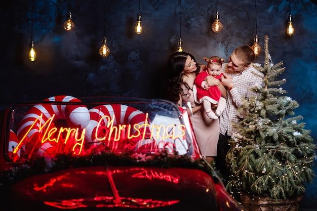 Mama, papa und baby haben spaß in der nähe von weihnachtsbaum und retro rotes auto.