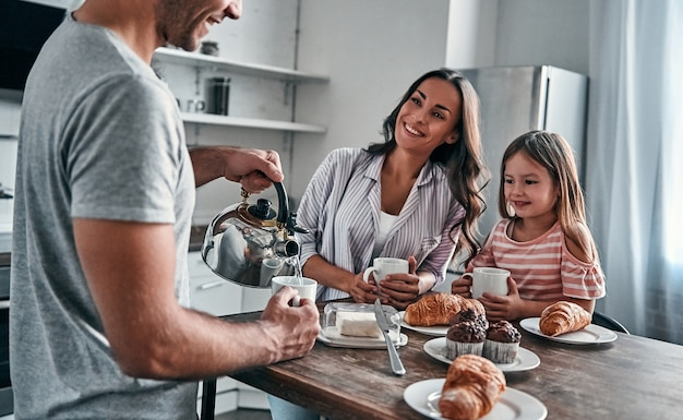 Mama, papa und ihre kleine schöne tochter haben eine teeparty in der küche und unterhalten sich. glückliches familienkonzept.