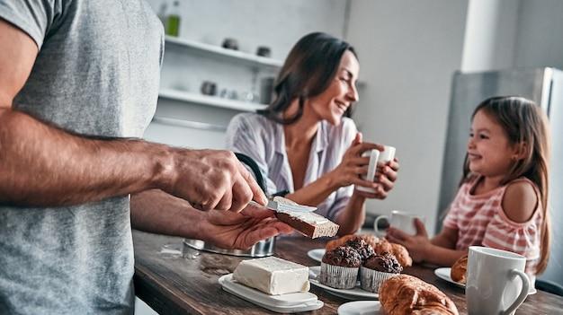 Mama, papa und ihre kleine schöne tochter haben eine teeparty in der küche und unterhalten sich. vater legt butter aufs brot. glückliches familienkonzept.
