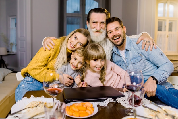 Mama, papa und ihre kleinen kinder, großvater essen im urlaub zu abend, sitzen am tisch in einem gemütlichen raum, benutzen laptop und reden