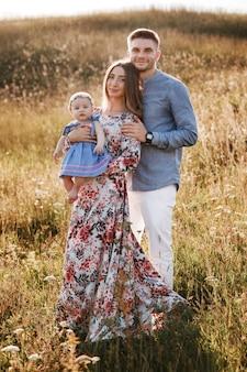 Mama, papa und kleine frau, die spaß draußen im gras am sommertag haben. mutter-, vater- und babytag. glückliche familie für einen spaziergang.