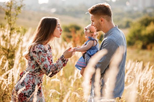 Mama, papa und kleines mädchen haben spaß im freien im gras am sommertag. mutter-, vater- und babytag. glückliche familie für einen spaziergang.