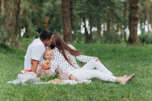Mama, papa und tochter sitzen auf dem picknick im park, wald. das konzept der sommerferien. vatertag, muttertag, babytag. zeit zusammen verbringen. familienlook. paar küssen