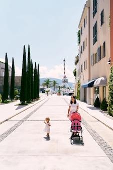 Mama rollt den kinderwagen die stadtstraße entlang und das kleine mädchen geht in der nähe spazieren