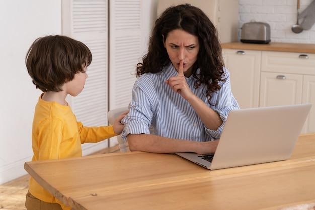 Mama sitzt am tisch im büro zu hause während der sperrung, arbeitet an laptop und kind lenkt ab und macht lärm
