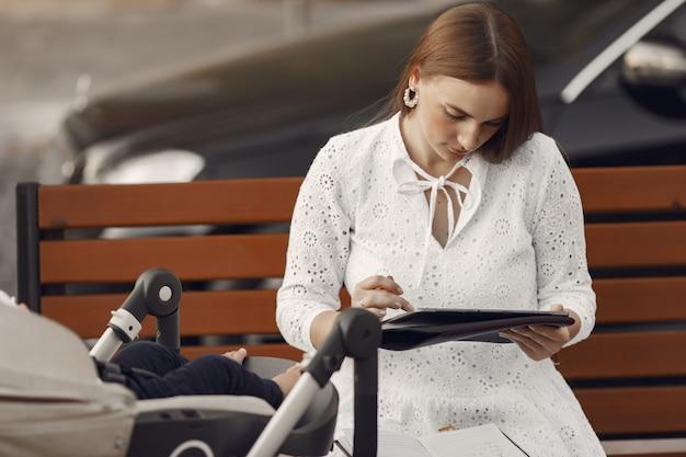 Mama sitzt auf einer bank. frau, die ihr kleinkind schiebt, das in einem kinderwagen sitzt. dame mit einer tablette.