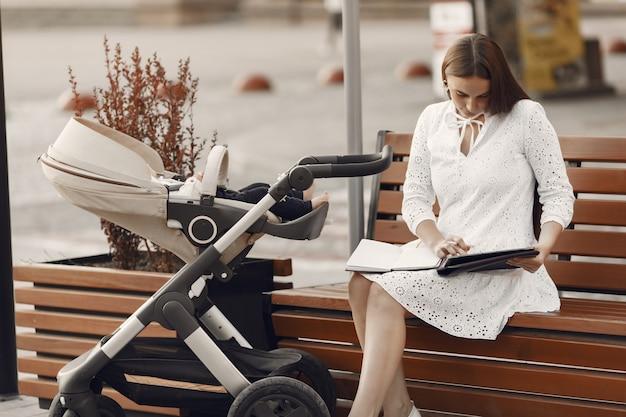 Mama sitzt auf einer bank. frau, die ihr kleinkind schiebt, das in einem kinderwagen sitzt. dame mit einer tablette