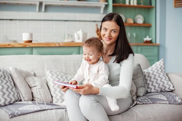 Mama sitzt mit einem kind auf einem sofa, liest ein buch und schaut sich helle bilder an