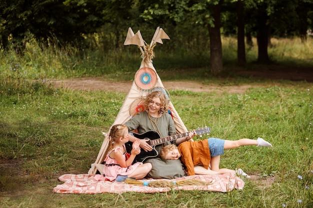 Mama spielt ihren kleinen töchtern im sommer neben der wigwam-dekoration im freien gitarre. gemeinsam sommerferien verbringen.