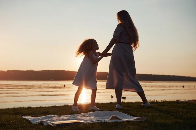 Mama spielt mit ihrem baby in den ferien in der nähe des ozeans, silhouetten bei sonnenuntergang