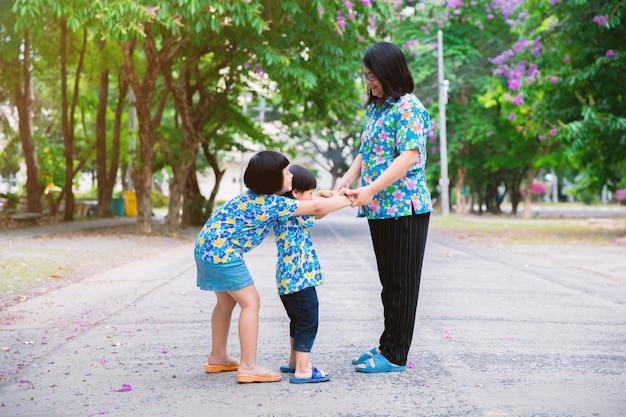 Mama spielt mit kindern im park.