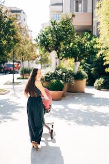 Mama steht mit einem kinderwagen in der nähe von wannen mit grünen büschen, die sich umdrehen