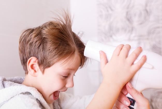 Mama trocknet babyhaar mit einem haar trocknet