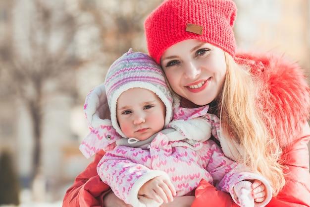 Mama umarmt ihre tochter beim gehen an einem sonnigen wintertag