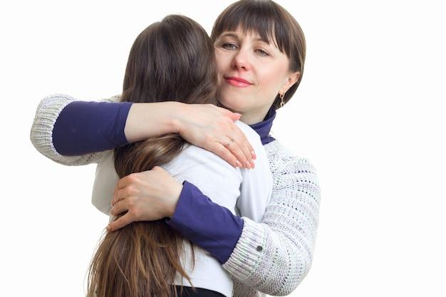Mama umarmt ihre tochter im studio fest auf weiß