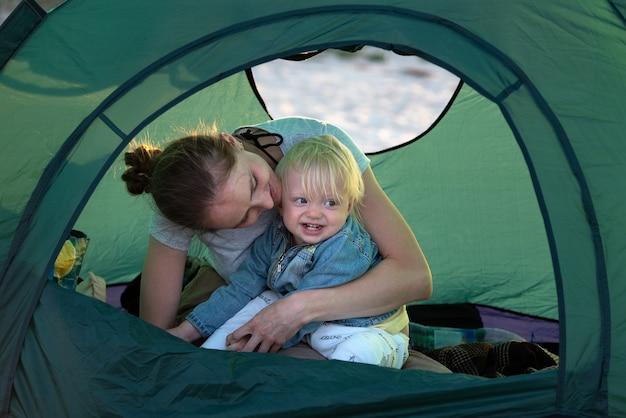 Mama umarmt kleines kind im touristenzelt auf dem campingplatz. aktive erholung mit kindern.