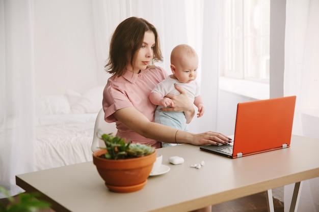 Mama und baby. eine junge mutter, die zu hause mit einem laptop arbeitet.
