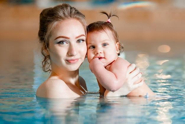 Mama und baby schwimmen im pool.