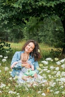 Mama und baby sitzen in einem park unter einem baum zwischen den blumen und lächeln. blumenfeld, picknick im freien.
