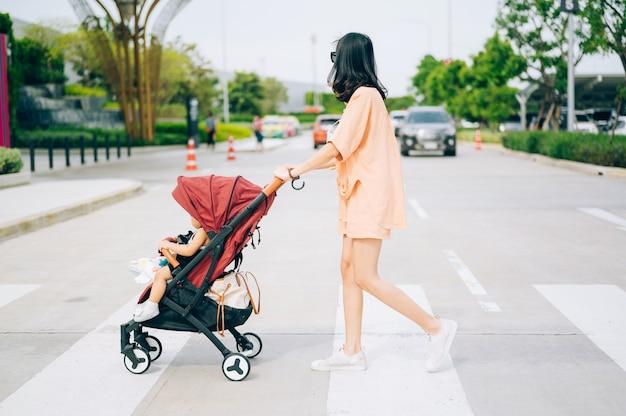 Mama und der kleine sohn auf dem kinderwagen überqueren die straße