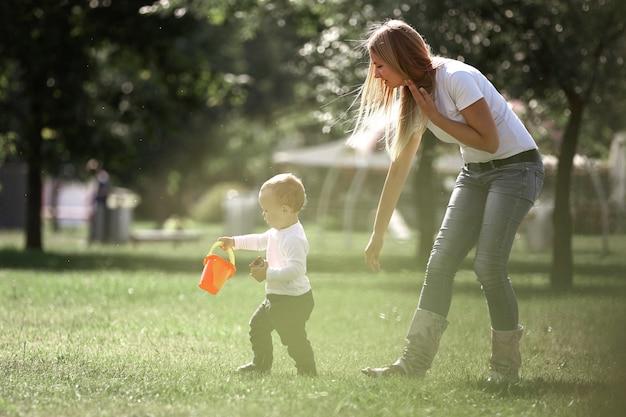 Mama und ihr kleiner sohn bei einem spaziergang im stadtpark. das konzept der aktiven erholung