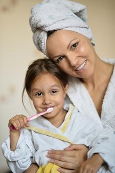 Mama und ihre kleine tochter beim zähneputzen