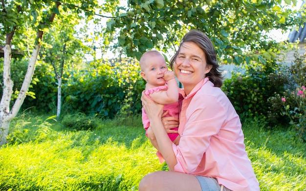 Mama und ihre kleine tochter lachen und haben spaß draußen im garten draußen.