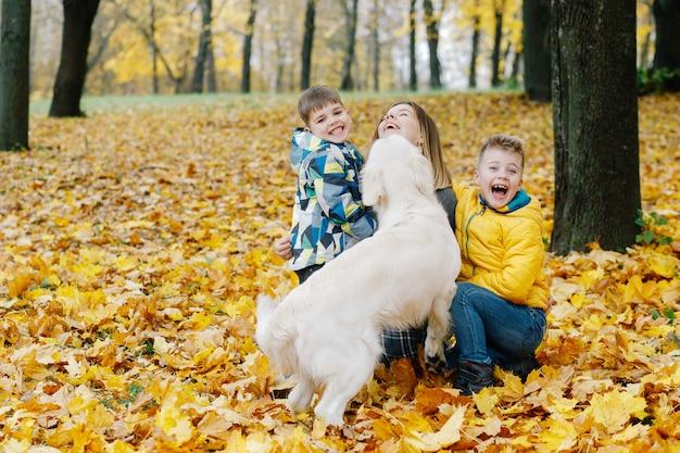 Mama und ihre söhne spielen im herbst mit einem hund im park
