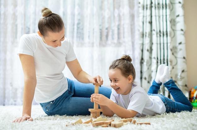 Mama und ihre tochter spielen zu hause zusammen auf dem boden. glücklich und lächelnd