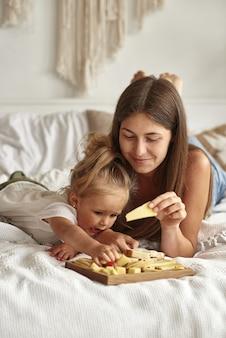 Mama und jüngste tochter probieren käse auf dem bett.
