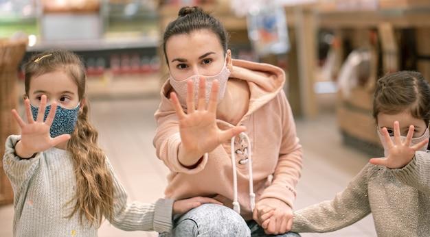 Mama und kinder kaufen im supermarkt ein. sie tragen während der quarantäne masken. coronavirus-pandemie .coved-19 flash. die epidemie des virus