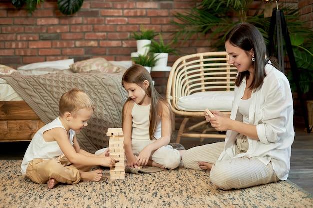 Mama und kinder spielen squirl tower. frau mädchen und junge spielen familienpuzzlespiel