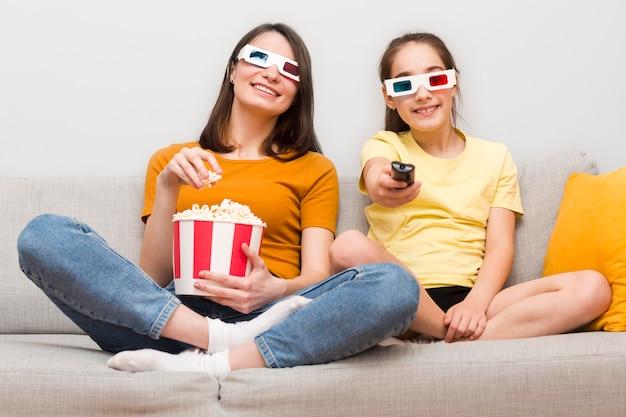 Mama und mädchen essen popcorn