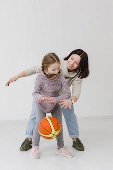 Mama und mädchen spielen basketball