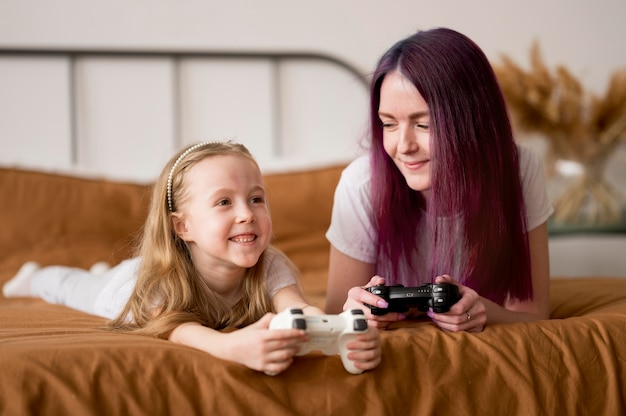 Mama und mädchen spielen mit joystick