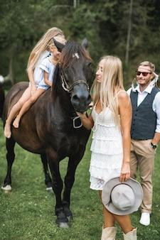 Mama und papa gehen mit ihren zwei kleinen süßen töchtern auf einem pferd in der natur spazieren
