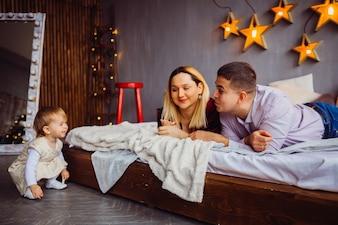 Mama und Papa lächeln zu kleinen Mädchen auf dem Bett liegen