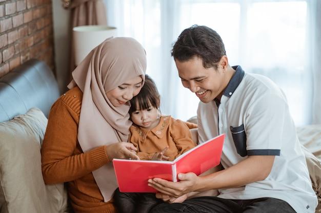 Mama und papa lächeln und halten ein buch in der hand, als sie ein geschichtenbuch mit ihrer tochter sehen