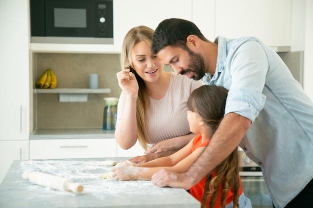 Mama und papa lehren kind, teig auf küchentisch mit mehl unordentlich zu kneten. junges paar und ihr mädchen backen brötchen oder kuchen zusammen. familienkochkonzept