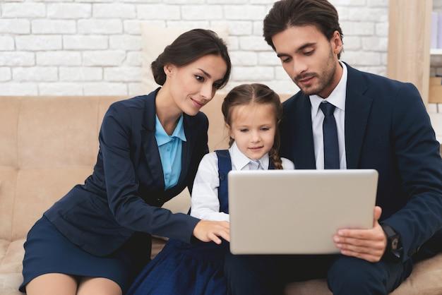 Mama und papa mit eingeschalteter tochter schauen auf den laptop.