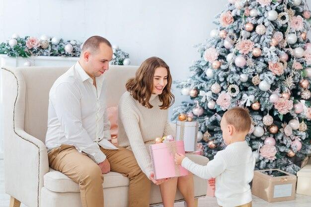 Mama und papa öffnen geschenke mit ihrem sohn