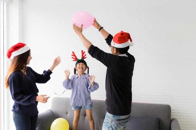 Mama und papa werfen luftballons, spielen mit ihren töchtern, lachen, lächeln und haben in den weihnachtsferien spaß im wohnzimmer.