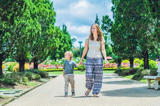 Mama und sohn gehen im tropischen park spazieren
