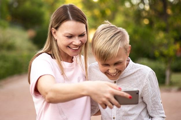 Mama und sohn lesen lustige geschichten auf dem smartphone
