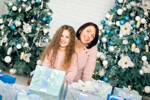 Mama und tochter, die geschenke einwickeln, um sich unter den weihnachtsbaum zu setzen