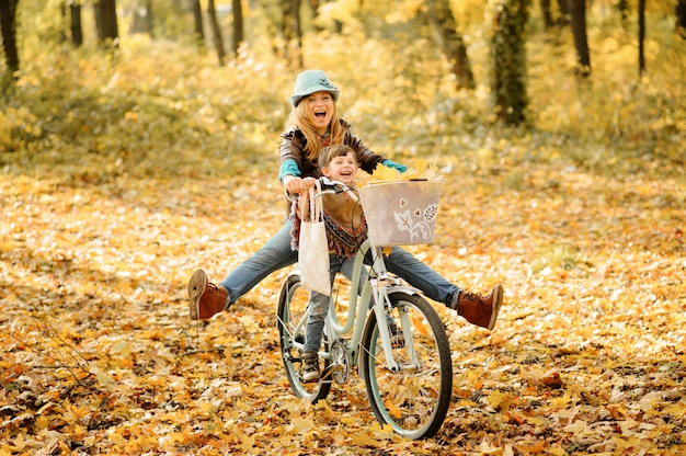 Mama und tochter haben spaß auf dem gleichen fahrrad. herbst fotoshooting.